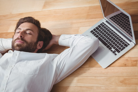 lying in: Business man lying on the floor in office Stock Photo