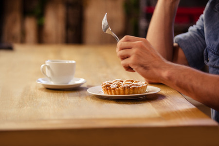 cropped image: Cropped image of hipster man eating and drinking coffee at cafe