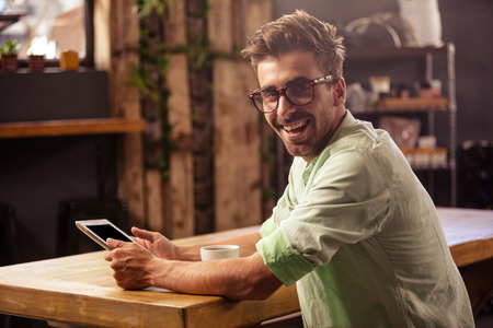 Happy hipster man posing for camera while using tablet at cafe
