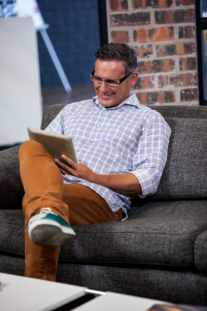 businessman working at his computer: Portrait of businessman smiling and working with his tablet computer on a sofa