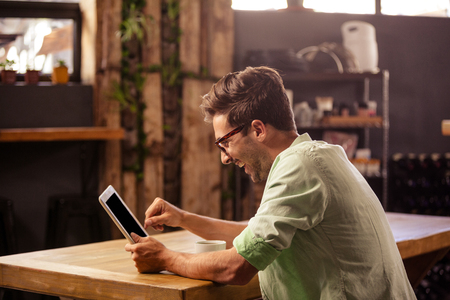 profile view: Profile view of hipster man using tablet at cafe Stock Photo