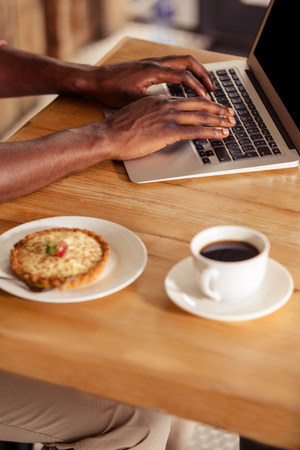 cropped image: Cropped image of casual man using laptop at coffee shop