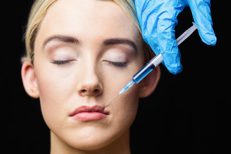 examination room: Woman receiving botox injection on her lips in a examination room Stock Photo