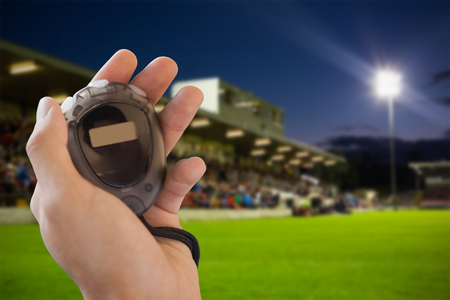 the stands: Close up of hand holding a stopwatch against pitch and stands Stock Photo