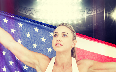 winning pitch: Female athlete holding American flag against american football arena