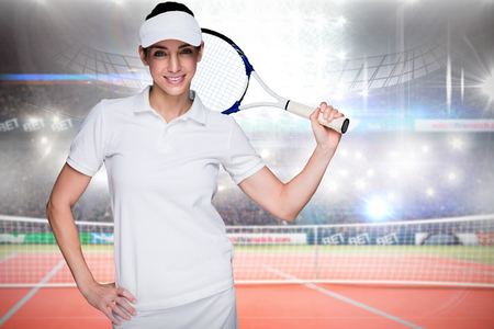 racket stadium: Composite image of sportswoman posing with a tennis racket in a stadium Stock Photo