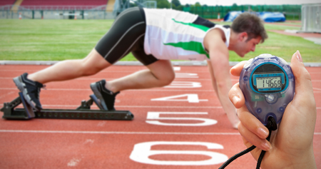 starting line: Composite image of a hand holding a timer against handsome sprinter on the starting line
