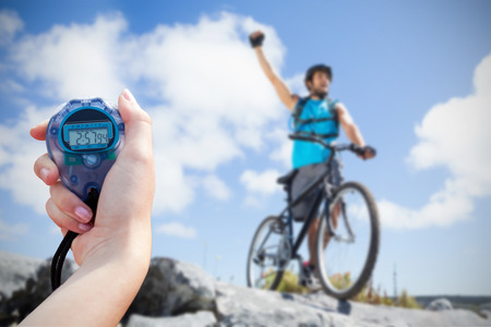 chronometer: Composite image of close-up of a woman holding a chronometer to measure performance of biker
