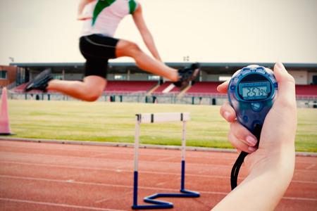 pies masculinos: Imagen compuesta de una mujer que sostiene un cronómetro para medir el desempeño contra las formas graves de saltar por encima de atleta masculino de cobertura durante una carrera Foto de archivo