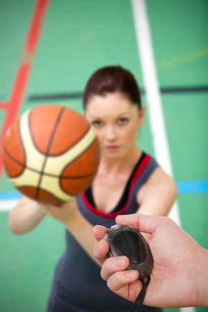 Close up of coach is holding a stopwatch  against portrait of a concentrated young woman playing basketball photo