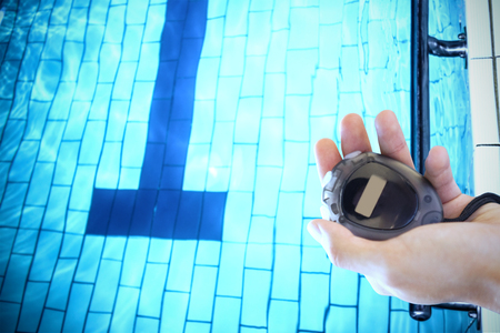 chronometer: Close up of a hand holding a chronometer close to the swimming pool