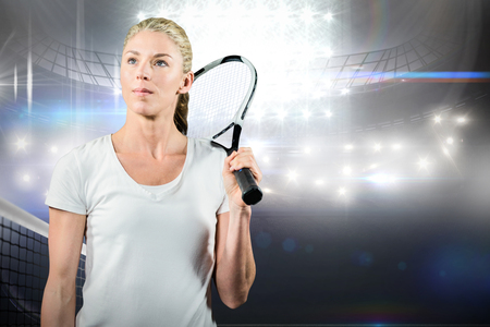 racket stadium: Female tennis player looking away with  her racket in a stadium