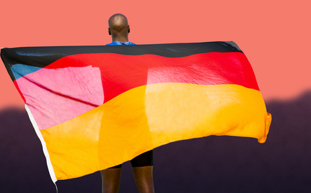 german flag: Rear view of sportsman is holding a german flag  against blurred mountains Stock Photo