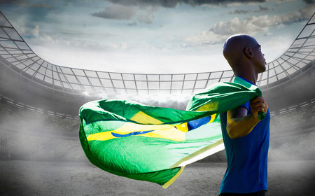 profile view: Profile view of sportsman holding a Brazilian flag  against stadium