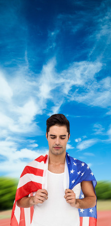 eyesclosed: Athlete with american flag wrapped around his body against athletics field on a sunny day