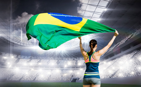 winning pitch: Rear view of sportswoman raising a brazilian flag  against sports arena