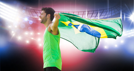 winning pitch: Profile view of Brazilian sportsman is holding a flag  against american football arena Stock Photo