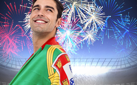 portugal flag: Athlete with portugal flag wrapped around his body against fireworks exploding over football stadium