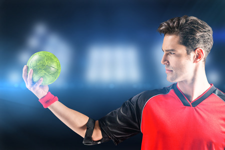 elbow band: Confident athlete man holding a ball  against composite image of spotlight