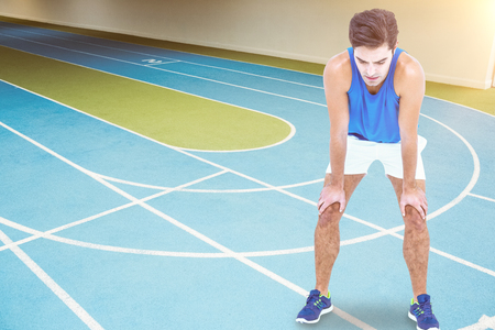 athletics track: Tired athlete standing with hand on knee against athletics track indoor Stock Photo