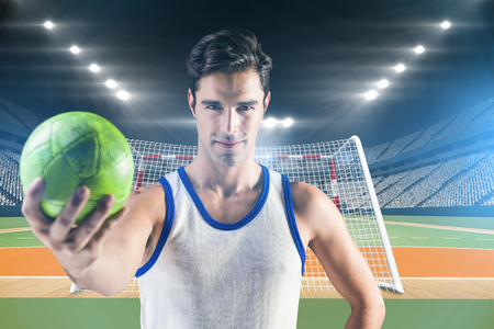 terrain de handball: Portrait d'athlète masculin heureux tenant un ballon contre terrain intérieur de handball