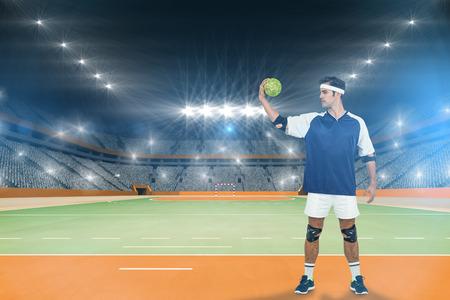 terrain de handball: Sportsman posant avec ballon sur fond blanc contre terrain intérieur de handball Banque d'images