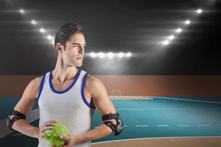 terrain de handball: Confiant athl�te homme tenant un ballon contre terrain int�rieur de handball Banque d'images