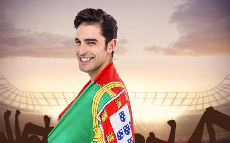 drapeau portugal: L'athlète avec le drapeau portugal enroulé autour de son corps contre le stade de football avec la foule en liesse Banque d'images