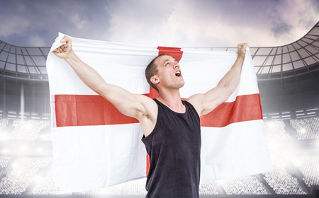 winning pitch: Athlete holding england national flag against sports arena