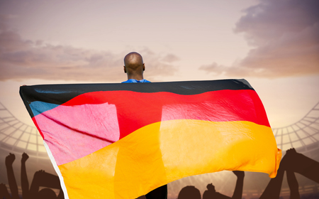 german flag: Rear view of sportsman is holding a German flag  against football stadium with cheering crowd