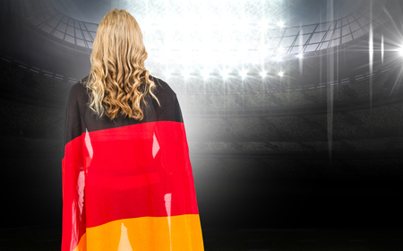 german flag: Athlete with german flag wrapped around his body against american football arena Stock Photo