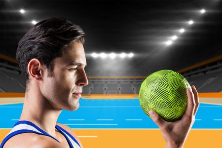 terrain de handball: Confiant athlète homme tenant un ballon contre terrain intérieur de handball Banque d'images