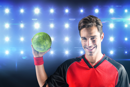 elbow band: Portrait of happy athlete man holding a ball  against composite image of blue spotlight
