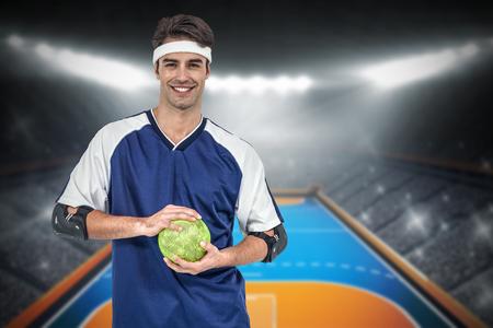 terrain de handball: Sportsman posant avec ballon sur fond blanc contre terrain int�rieur de handball Banque d'images