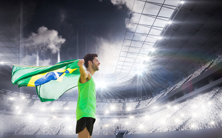 winning pitch: Profile view of Brazilian sportsman is holding a flag  against sports arena Stock Photo
