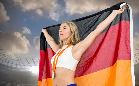 german flag: Athlete posing with german flag after victory against large football stadium under cloudy blue sky