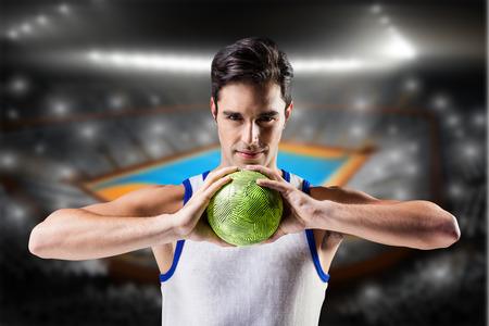 terrain de handball: Portrait d'un homme heureux athl�te tenant balle contre terrain int�rieur de handball