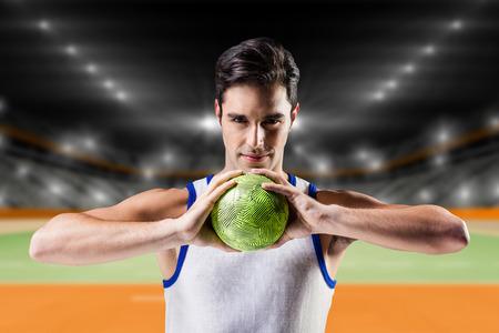 terrain de handball: Portrait d'un homme heureux athlète tenant balle contre terrain intérieur de handball