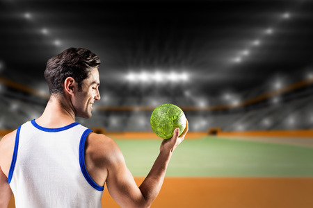 terrain de handball: Happy athlete male holding a ball  against handball field indoor Banque d'images