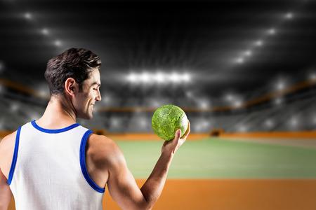 terrain de handball: Heureux athl�te masculin tenant un ballon contre terrain int�rieur de handball