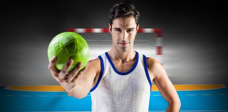 terrain de handball: Portrait d'athl�te masculin heureux tenant un ballon contre terrain int�rieur de handball