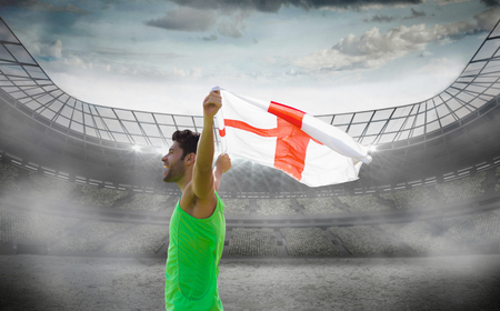 profile view: Profile view of sportsman holding an England flag against stadium Stock Photo