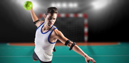 terrain de handball: Confiant athlète homme lancer une balle contre terrain intérieur de handball