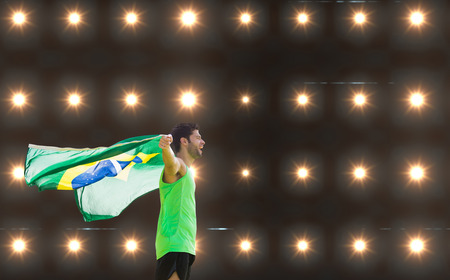profile view: Profile view of Brazilian sportsman is holding a flag  against composite image of orange spotlight Stock Photo