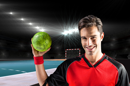 elbow band: Portrait of happy athlete man holding a ball  against handball field indoor
