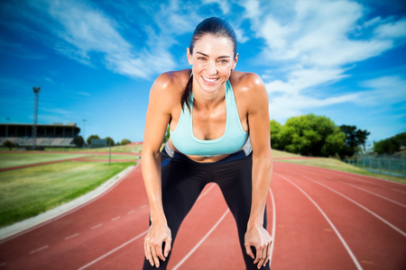 legging: Sportswoman posing his hands on knee against high angle view of track