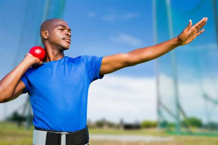 lanzamiento de bala: Vista frontal del deportista practicando lanzamiento de peso contra el campo deportivo en un día soleado