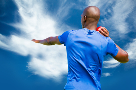 lanzamiento de bala: Rear view of sportsman is practising shot put  against blue sky with clouds
