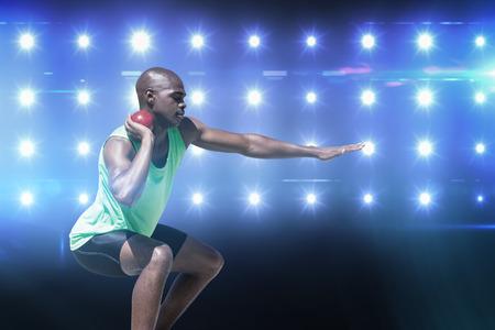 lanzamiento de bala: Deportista practicando el lanzamiento de peso en contra de imagen compuesta de azul foco Foto de archivo