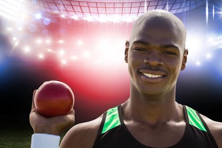 lanzamiento de bala: Retrato de deportista feliz está sosteniendo un lanzamiento de peso en contra de campo de fútbol americano Foto de archivo